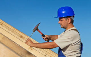 Construction worker on roof hammering