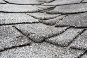 Closeup photo of shingles on an old composite roof that show damage and cause of roof leaks